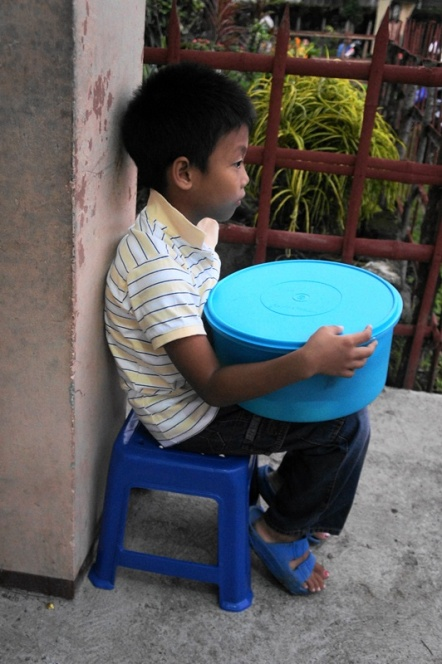 A local boy waits near the entrance door with his mamon.