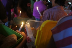 Lighted candles and open boxes of mamon signal that the time for the blessing rites is about to begin. The priest then says his benediction and sprinkles the Holy water throughout the crowd.