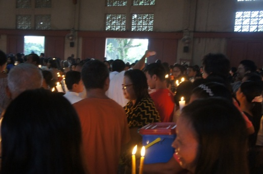 The priest (center in white robe) blessing the candles, mamon and other items brought by the parishioners to the church.