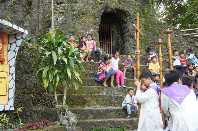 Children sit at the steps of the belfry during the First Day of Lent event in Bulusan, March, 9, 2014.
