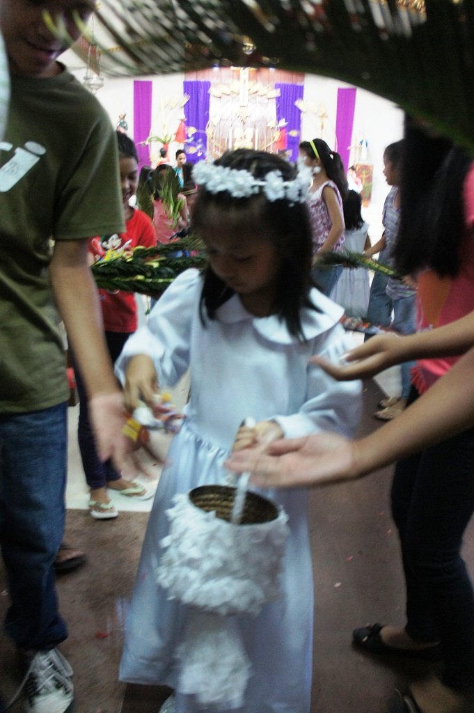 Hosanna choir girl giving away flower petals from her basket after the Palm Sunday mass.