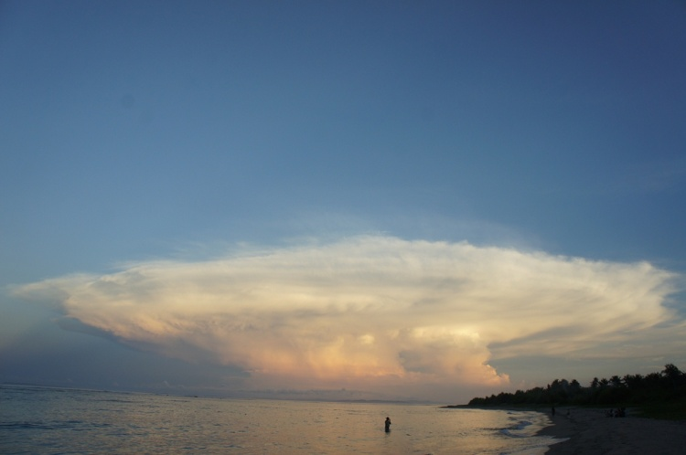 A late afternoon dip for this Dancalan beach tourist with spectacular cloud formation as backdrop .
