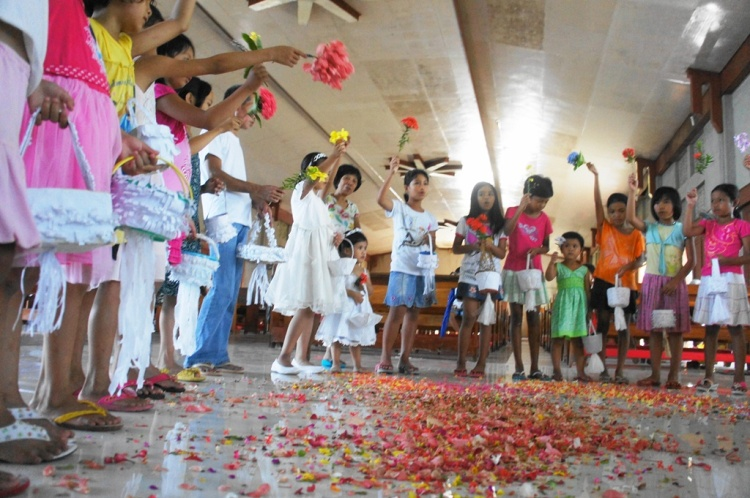 Local children singing hymns and offering flowers and petals confetti to the Blessed Virgin Mary at the church in Bulusan.