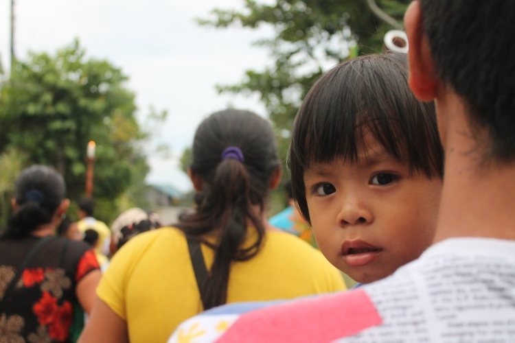 A boy stares into my camera during the procession.
